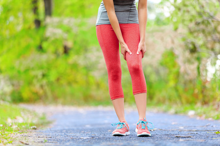 Sports muscle injury of female runner thigh. Woman running muscle strain injury in thigh. Closeup of runner touching leg in muscle pain.
