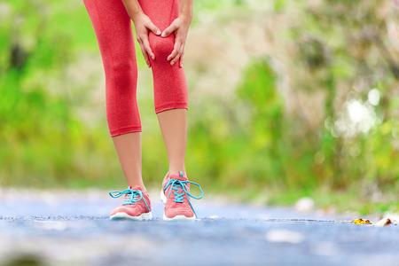 de rodillas: Lesión de rodilla - deportes que ejecutan las lesiones de rodilla en la mujer. Corredor femenino con dolor de rodilla esguince. Cerca de las piernas, los músculos y la rodilla al aire libre en el bosque. Foto de archivo