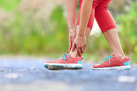 sprain: Twisted broken ankle - running sport injury. Female runner touching foot in pain due to sprained ankle.