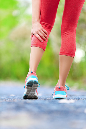 calf strain: Muscle injury - woman running clutching calf muscle after spraining it while out jogging on the beach. Female athlete sport injury.