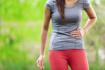 tired: Side stitch - woman runner side cramps after running. Jogging woman with stomac side pain after jogging work out. Female athlete. Stock Photo