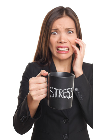 stressed: Stress concept. Business woman stressed being too busy. Businesswoman in suit holding head drinking coffee creating more stress. Mixed race Asian Caucasian female isolated on white background.