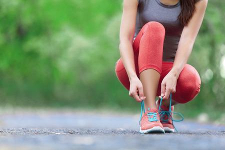 здравоохранение: Кроссовки - крупным планом женщина связывая шнурки. Женский спортивный фитнес бегун готовится для бега на открытом воздухе на лесной тропинке весной или летом.