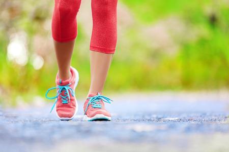 Mujer que activa con las piernas atléticas y zapatillas deportivas. Mujer caminando en el sendero en el bosque en concepto de estilo de vida saludable con el primer plano de los zapatos para correr. Entrenamiento femenino basculador atleta al aire libre.