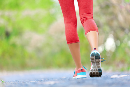 Woman with athletic legs on jog or run on trail in forest in healthy lifestyle concept with close up on running shoes. Female athlete jogging and training outdoors.