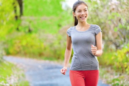 Mujer caminando potencia velocidad nórdico, trotar y correr suavemente en el bosque en primavera o verano. La aptitud del entrenamiento de la muchacha deportiva y la elaboración de vivir el estilo de vida saludable y activo en el bosque de Deporte. Foto de archivo