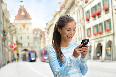 tour guide: Mujer en el tel�fono inteligente en pie Kramgasse, Berna calle principal de la ciudad vieja. Hembra joven que usa smartphone app visitar las atracciones tur�sticas y lugares de inter�s.