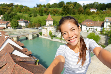 people travelling: Travel selfie by woman in Bern Switzerland. Happy smiling multiracial Asian Caucasian girl taking self portrait photograph sitting on Nydeggbrucke by Aare river in the Swiss city of Bern.