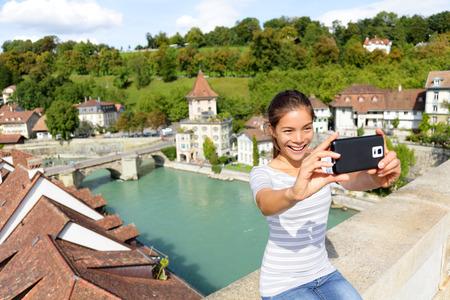 Voyage téléphone intelligent selfie par la femme à Berne en Suisse, en Europe. Sourire heureux multiraciale fille asiatique de prendre l'auto photo portrait assis sur le pont Nydegg par la rivière Aar dans la ville suisse de Berne