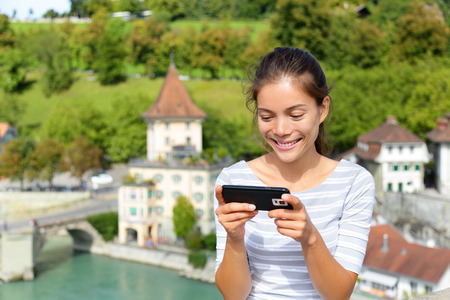 travel guide: Woman using smart phone app in Bern Switzerland, Europe. Person using smartphone application on travel. Happy smiling Asian girl sitting on Nydegg bridge by the Aare river in the Swiss city of Berne