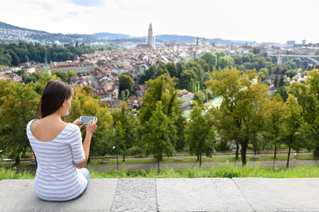 rosengarten: Tourist with smart phone camera in Bern, Switzerland at Rosengarten, the Rose Garden view. Woman taking photograph with smartphone at enjoying view of Berne landmarks and tourist attractions.