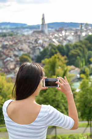 rosengarten: Tourist with smartphone camera in Bern, Switzerland at Rosengarten, the Rose Garden view. Woman taking photograph with smartphone at enjoying view of Berne landmarks and tourist attractions. Stock Photo