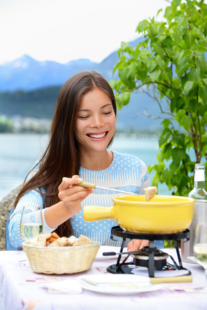 swiss culture: Cheese fondue - woman eating local Swiss food. People eating traditional food from Switzerland having fun by lake in the Alps on travel in Europe.