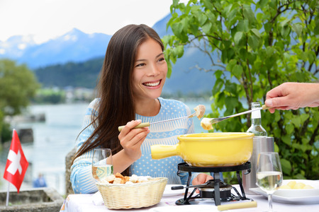 swiss culture: People eating Swiss cheese fondue having dinner in Switzerland by lake in Alps. Woman eating local food having fun on travel in Europe. Romantic couple outdoors in summer.