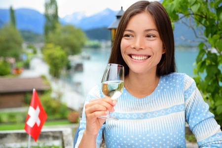 Woman drinking wine at dinner in Switzerland. Asian woman enjoying glass of white wine in the Swiss Alps by lake in summer.