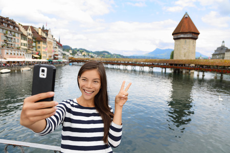 Tourist selfie woman taking self portrait photograph picture with smartphone in Lucerne Switzerland. Travel woman with smart phone by Kapellbrücke Chapel Bridge and Wasserturm water tower, Reuss River