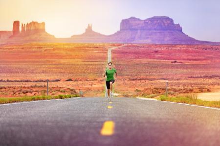 deportista: Runner hombre atleta que corre carreras de velocidad en la carretera por el valle del monumento. Concepto con el velocista entrenamiento r�pido para el �xito. Modelo de la aptitud deportiva en forma de trabajo en la sorprendente paisaje de la naturaleza. Arizona, Utah, EE.UU.. Foto de archivo