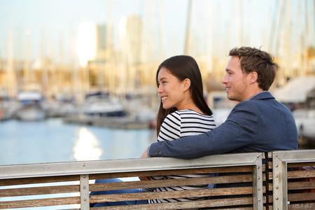 ロマンチックなカップルは古いポート Vell 港、カタルーニャ、スペインのバルセロナでベンチに座っています。幸せな女と男の人生を楽しむと外の 写真素材