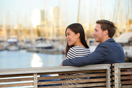 Romantic couple sitting on bench in old harbour, Port Vell, Barcelona, Catalonia, Spain. Happy woman and man embracing enjoying life and romance outside. Multiracial Caucasian Asian couple in love.