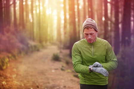 Trail running runner looking at heart rate monitor watch running in forest wearing warm jacket sportswear, hat and gloves. Male jogger running training in woods.