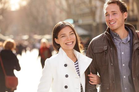 caminando: Urbano moderno j�venes profesionales pareja caminando rom�ntico riendo hablando de la mano en la fecha. Pareja multicultural C�ucaso y Asia joven en La Rambla de Barcelona, ??Catalu�a, Espa�a.