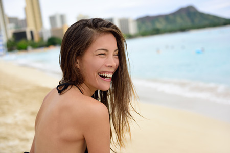 diamond head: Laughing beach woman in bikini having fun on Waikiki, Oahu, Hawaii, USA. Portrait of girl on travel vacation holidays in laughter on Hawaiian Waikiki beach with Diamond Head. Asian Caucasian model.