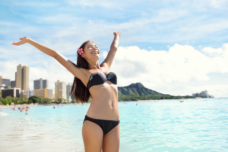 diamond head: Beach woman in bikini happy and free on Waikiki, Oahu, Hawaii, USA. Girl on travel vacation holidays having fun on Hawaiian Waikiki beach with Diamond Head mountain. Asian Caucasian model. Stock Photo