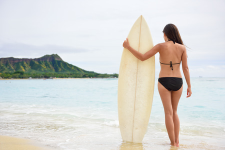 surfboard: Surfer woman going surfing standing with surfboard on Waikiki Beach, Oahu, Hawaii. Female bikini girl walking with surfboard living healthy active lifestyle on Hawaiian beach. Asian Caucasian model. Stock Photo