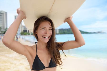 asian bikini: Portrait of surfer woman on Waikiki Beach, Oahu, Hawaii. Female bikini girl walking with surfboard smiling happy having fun living healthy active lifestyle on Hawaiian beach. Asian Caucasian model. Stock Photo