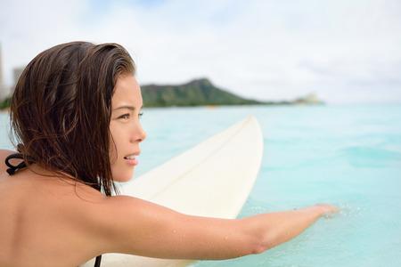 asian bikini: Surfer girl surfing paddeling on surfboard. Female surf bikini woman living healthy active water sports lifestyle on Hawaiian beach. Asian Caucasian model on Waikiki Beach, Oahu, Hawaii.