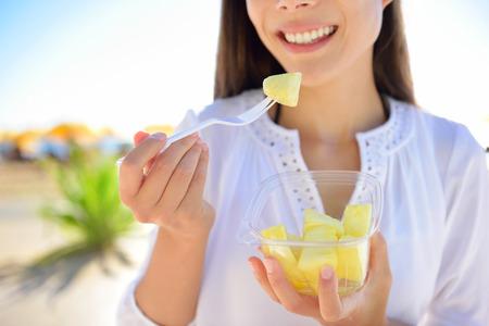 パイナップル - を食べる女性は取る離れてボウルから健康的なおやつとしてハワイアン パイナップル果実をスライスしました。