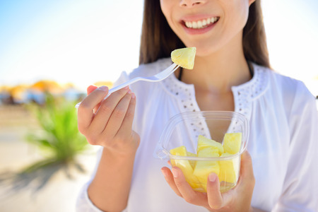 Pineapple - woman eating sliced Hawaiian pineapple fruit as a healthy snack from take away bowl.