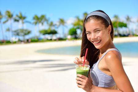 the juice: Green detox smoothie - woman drinking vegetable smoothie after fitness running workout on summer day. Fitness and healthy lifestyle concept with beautiful fit mixed race Asian Caucasian model.