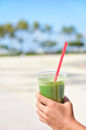 jugo verde: Smoothie de vegetal verde - concepto de alimentaci�n saludable. Close up de color verde desintoxicaci�n vegetal licuado con espinacas. Mano de mujer con los batidos de verduras al aire libre en la playa de verano. Foto de archivo