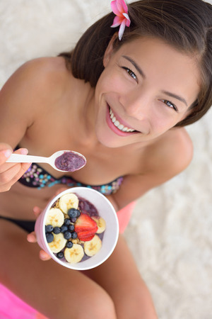 Acai bowl - woman eating healthy food on beach. Girl enjoy acai bowls made from acai berries and fruits outdoors on beach for breakfast. Girl on Hawaii eating local Hawaiian dish.