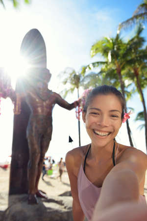 Waikiki Beach Tourist in Honolulu on Oahu, Hawaii taking selfie self portrait photograph in front of famous tourist attraction and surfing landmark, the statue of Duke Kahanamoku. Travel on Hawaii. photo