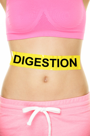 Digestion Concept - Close up Woman Stomach with Digestion Text on Yellow Tape. Isolated on White Background.