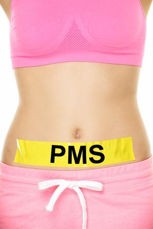 emphasising: PMS Sindrome premestruale Concept - Bare donna Stomaco con nastro giallo Sottolineando PMS Testi. Catturato su sfondo bianco. Archivio Fotografico