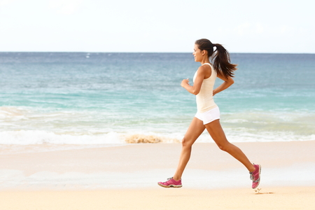 running pants: Fit young woman running along the edge of the surf on a sunny tropical beach in her sportswear with her long hair. Fenake runner exercising with copyspace
