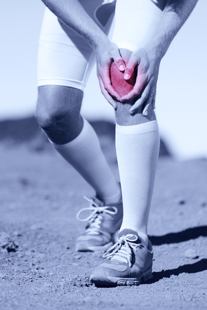 Greyscale image of the legs of a sportsman with a knee injury clasping his knee depicted in red selective color conceptual of a pulled muscle, cartridge, strain, sprain or tendon injury
