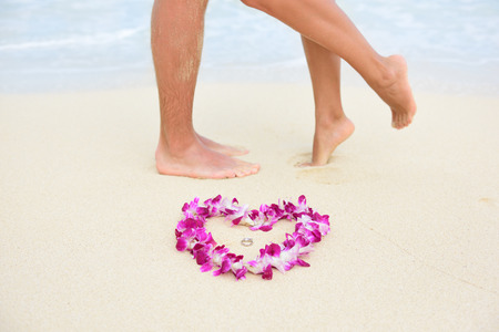 Beach wedding just married couple kissing with feet in background and rings in focus in heart shape lei flower necklace. Hawaiian marriage love concept. Stock Photo