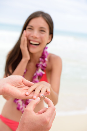 proposing: Marriage proposal casual couple beach wedding concept. Man proposing to girlfriend during holiday travel. Young lovers in love.