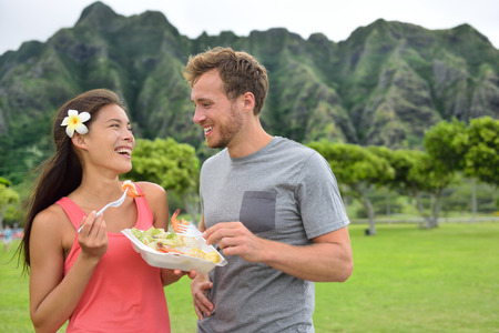 shrimp: Hawaii food travel couple eating garlic shrimps on Oahus North Shore. Popular Hawaiian shrimp food truck meal on road trip concept.