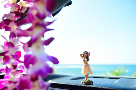 hula girl: Hawaii travel car - Hula girl dancing on dashboard and lei during road trip.