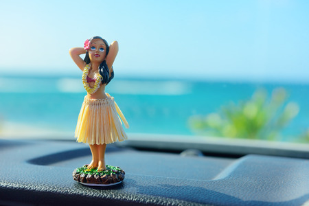 Hawaii road trip - car hula dancer doll dancing on the dashboard in front of the ocean. Tourism and travel freedom concept. Foto de archivo