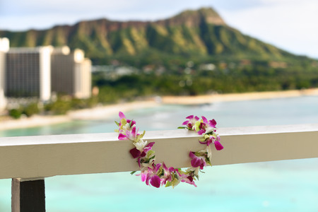 balcony view: Hawaii travel icon: Lei flower necklace in front of Waikiki beach and Diamond Head state monument in Honolulu Stock Photo