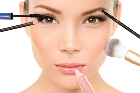 mujer maquillandose: Concepto Maquillaje - mujer asiática con muchos pinceles contra cara de la belleza que pone el rimel, rubor y brillo de labios Foto de archivo