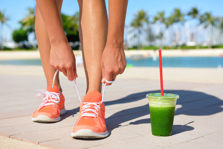 Running woman runner with green vegetable smoothie.  Fitness and healthy lifestyle concept with female model tying running shoe laces. Banque d'images
