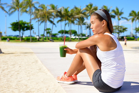Healthy woman runner drinking green vegetable smoothie resting and relaxing after running.  Fitness and healthy lifestyle concept with multicultural Asian Caucasian female model.