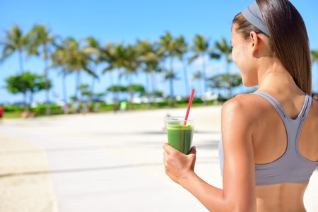 Woman drinking vegetable Green detox smoothie after fitness running workout on summer day. Fitness and healthy lifestyle concept with beautiful fit mixed race Asian Caucasian model outside on beach.